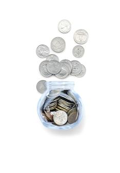 Monete in vaso di vetro dei soldi e trabocco isolato su bianco