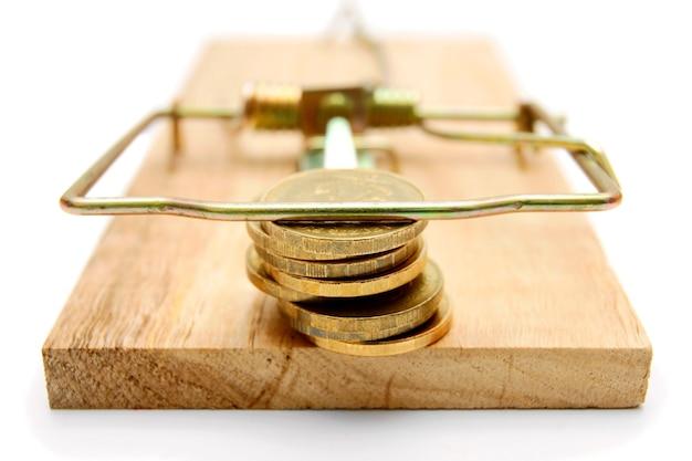 Monete in trappola per topi. su un tavolo bianco.