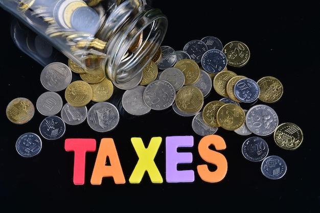 Monete che fuoriescono da un barattolo di soldi con la parola tasse