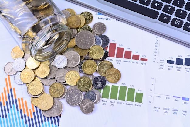 Monete che fuoriescono dal barattolo sui grafici delle azioni aziendali - business concept