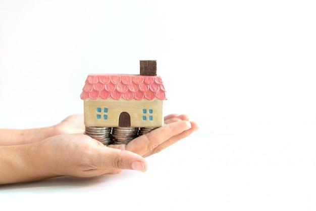 Le monete impilano per i soldi di risparmio e il modello domestico in mani, i piani di risparmio per l'alloggiamento del concetto finanziario, lo spazio della copia, fine su