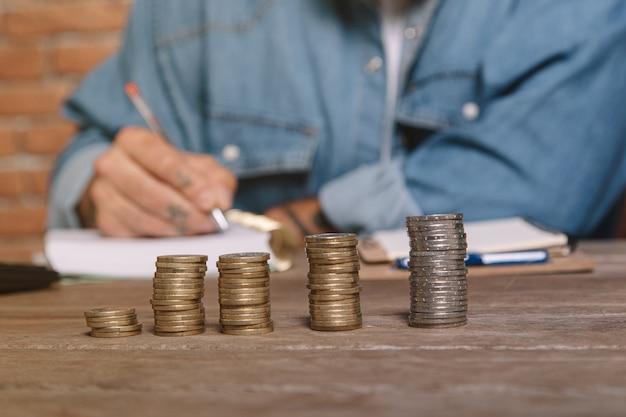Monete impilate in primo piano e uomo che annota le spese in un taccuino per calcolare il concetto di risparmio di denaro per la contabilità domestica.