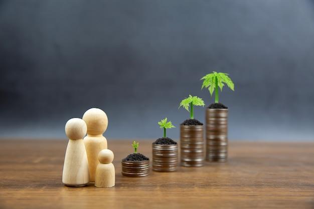 Monete impilate in un grafico con il simbolo della famiglia e l'alberello di un albero in crescita.
