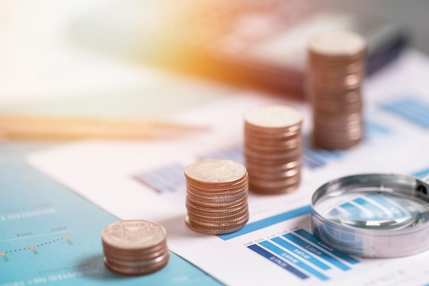 Monete che si impilano sulla relazione finanziaria con lente d'ingrandimento e calcolatrice.
