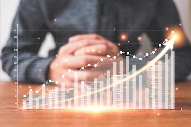 Monete che impilano con il grafico virtuale e aumentano la freccia davanti all'uomo d'affari. investimento aziendale e concetto di profitto di risparmio.