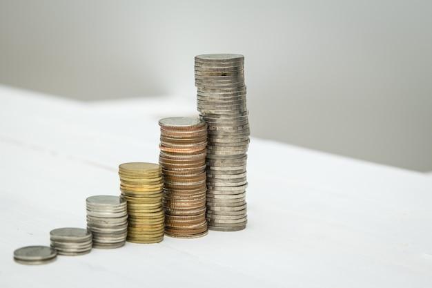 Monete che impilano sui precedenti bianchi di legno