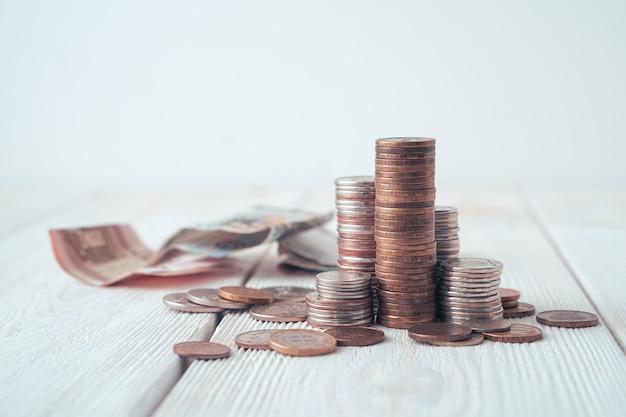 Monete in pile e banconote sullo sfondo di uno sfondo sfocato su uno sfondo chiaro.