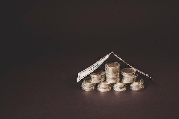 Pile di monete coperte dalla fattura sotto forma di casa concetto di risparmio di denaro investimento di reddito