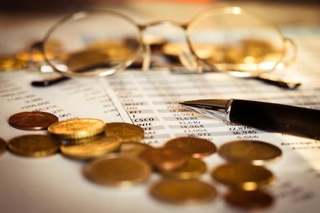 Monete con carta finanziaria e bicchieri