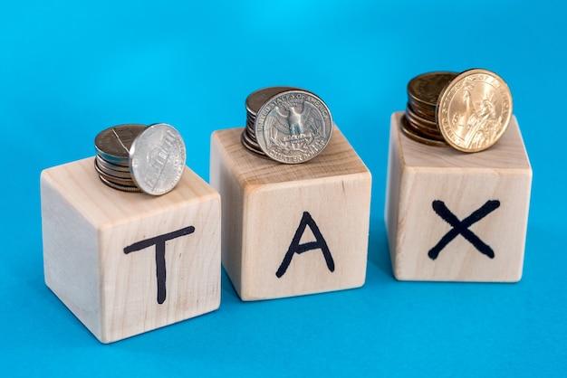 Monete con cubi di legno e testo di imposta. tempo di concetto per le tasse.
