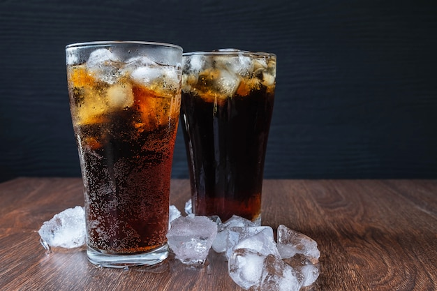 Cola in vetro e cubetti di ghiaccio su fondo di legno