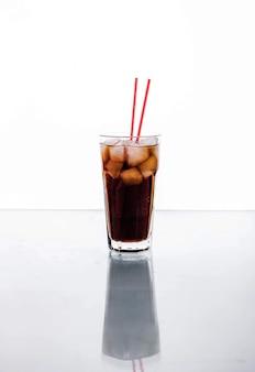 Cola in un bicchiere con ghiaccio con tubo rosso. bevande analcoliche