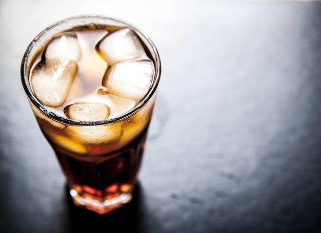 Cola con ghiaccio su uno sfondo di legno. bevande analcoliche
