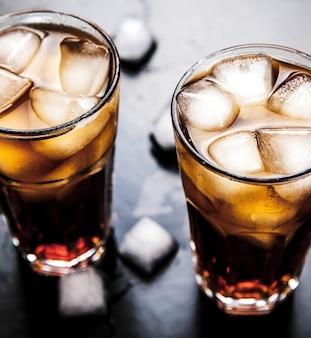 Cola con ghiaccio su un tavolo di legno. bevande analcoliche