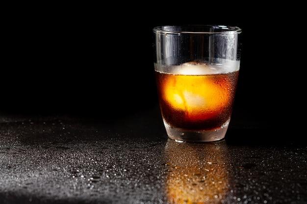Decorazione americana fredda con palla di ghiaccio nel bicchiere di whisky su un tavolo nero.