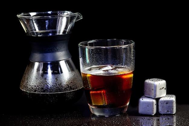 Decorazione americana fredda con cubetti di ghiaccio in acciaio inossidabile su un tavolo nero.