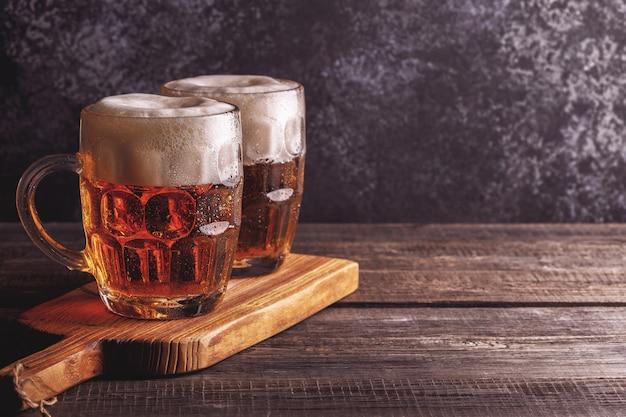 Birra fredda in vetro con patatine fritte su un buio.