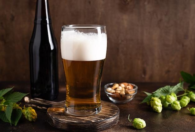Il bicchiere di birra fredda con snack in schiuma su sfondo di legno scuro beve il concetto di festa dell'alcool
