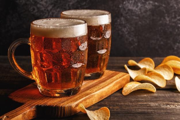 Birre fredde in vetro con patatine fritte su superficie scura