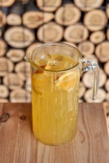Cocktail freddo agli agrumi con succo d'arancia e, menta e ghiaccio in un bicchiere con gocce. cocktail multicolore di alcol al bar.