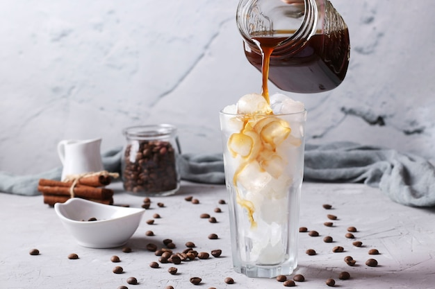 Il caffè freddo viene versato in un bicchiere alto con cubetti di ghiaccio su sfondo grigio chiaro