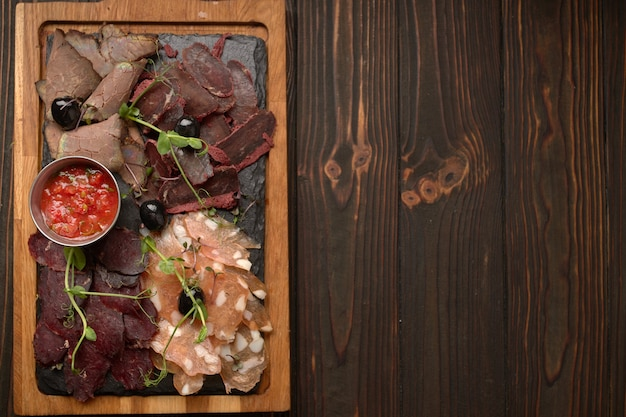 Salumi, salsiccia, basturma, carne affumicata, con salsa e olive, su una tavola di legno, su una tavola di legno