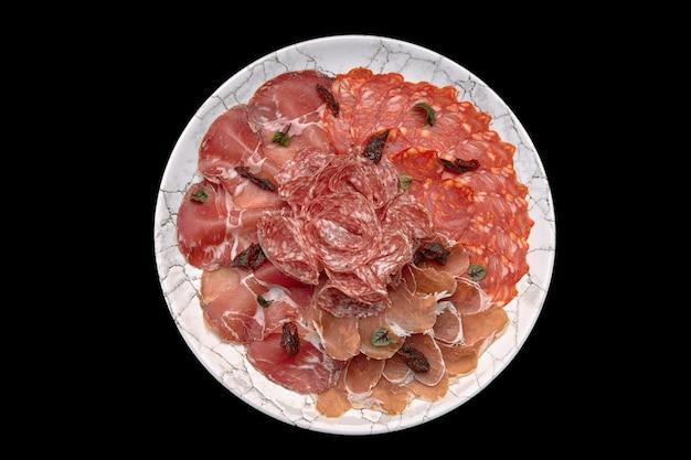 Salumi e salsiccia su piatto isolato su sfondo nero