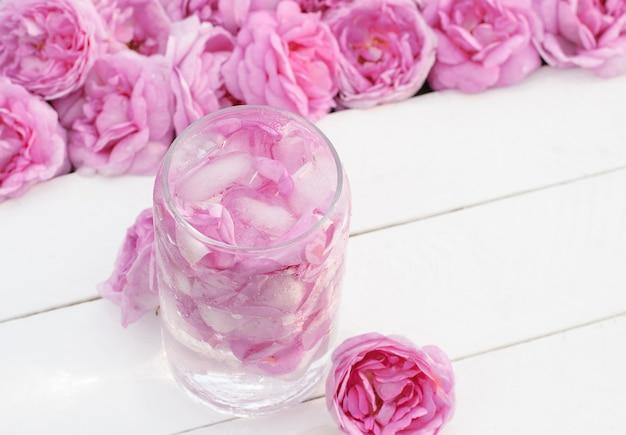 Bevanda fredda a base di petali di rosa tea rosa chiaro in un bicchiere su tavole di legno bianche con fiori di rosa