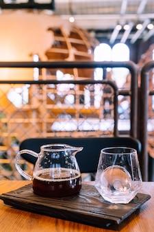 Barattolo di caffè nero a goccia fredda con vetro e ghiaccio nella caffetteria e ristorante