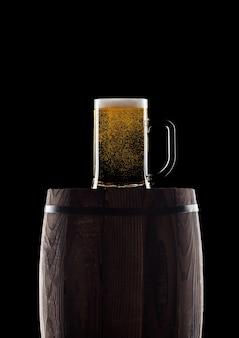 Bicchiere freddo di birra artigianale sulla vecchia botte di legno su sfondo nero con rugiada e bolle