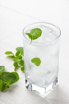 Bicchiere di acqua potabile fredda con ghiaccio e menta