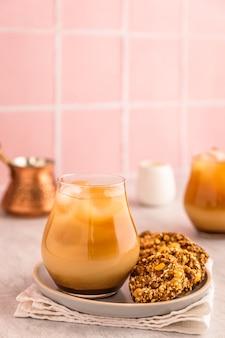 Caffè freddo con latte in un bicchiere, servito con biscotti di farina d'avena. un cezve e una brocca di latte bianco. luce calda e immagine verticale brillante, sfondo di piastrelle rosa