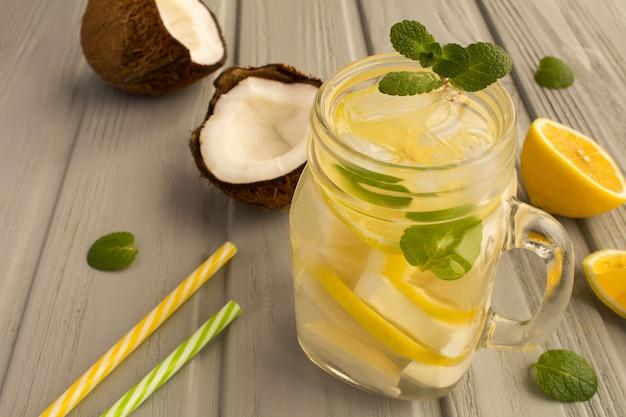 Limonata fredda con cocco, limone e menta su fondo di legno grigio