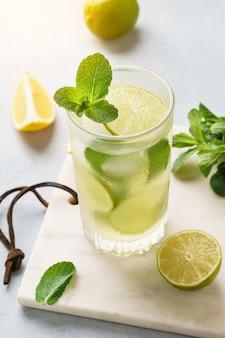 Limonata fredda con limone fresco, lime e menta in un bicchiere.