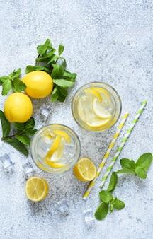 Limonata fredda con limone, menta e ghiaccio su uno sfondo di cemento.