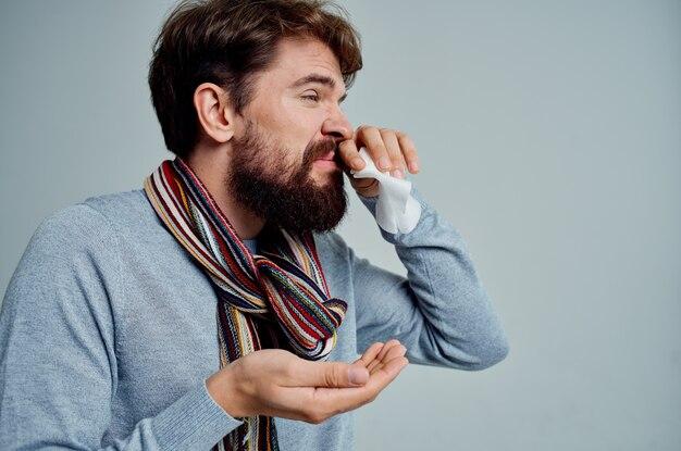 Uomo freddo in un maglione con uno sfondo chiaro di infezione da fazzoletto