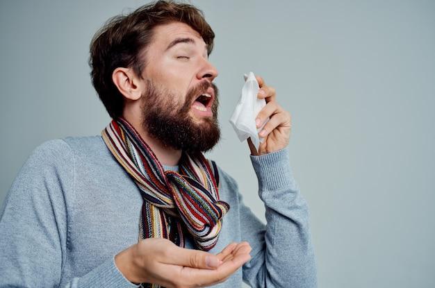 Uomo freddo che si pulisce il naso con un fazzoletto problemi di salute sfondo isolato. foto di alta qualità