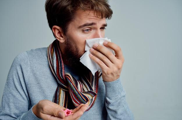 L'uomo freddo che si pulisce il naso con un fazzoletto ha isolato i problemi di salute sullo sfondo