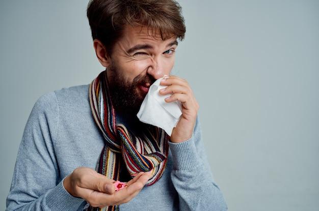 Uomo freddo con una sciarpa intorno al collo problemi di salute influenza sfondo chiaro