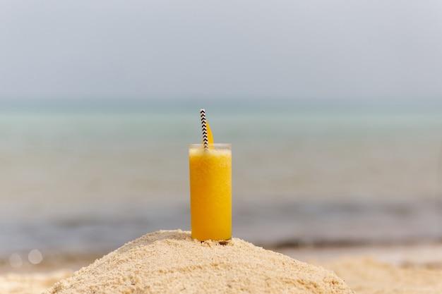 Bevanda fredda multi cocktail di frutta con fette di mango su sfondo spiaggia beach