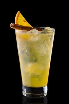 Bevanda rinfrescante fredda di arancia e cannella in un bicchiere alto isolato sul nero