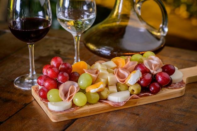 Piatto freddo e bicchieri di vino su un tavolo di legno.
