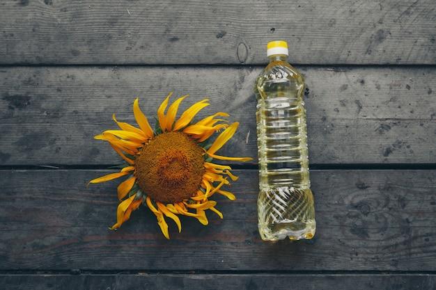 Olio spremuto a freddo e un bellissimo, grande girasole in fiore su uno sfondo di legno. petali di girasole gialli. uno sfondo naturale associato all'estate.
