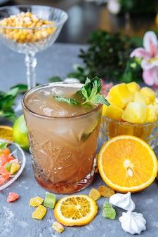 Cocktail di ananas rinfrescante freddo con lime e menta per una calda giornata estiva su un grigio