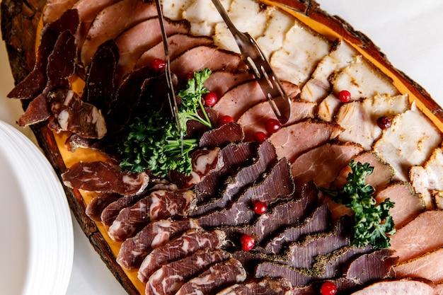 Piatto di carne affumicata a freddo con prosciutto, salame, pancetta e braciole di maiale.