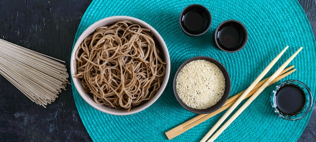 Soba freddo (spaghetti di grano saraceno) con salsa e sesamo. cibo giapponese. cucina asiatica tradizionale - tagliatelle di farina di grano saraceno. vista dall'alto, piatto. bandiera