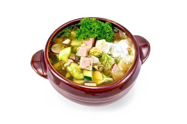 Zuppa fredda okroshka di salsiccia, patate, uova, ravanello, cetriolo, verdure e kvas in ciotola di argilla isolata su sfondo bianco