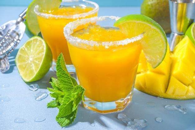 Cocktail estivo freddo, margarita al mango con tequila, fettine di lime e sale, ghiaccio tritato e menta. bevanda rinfrescante stagionale, su sfondo blu brillante illuminato dal sole