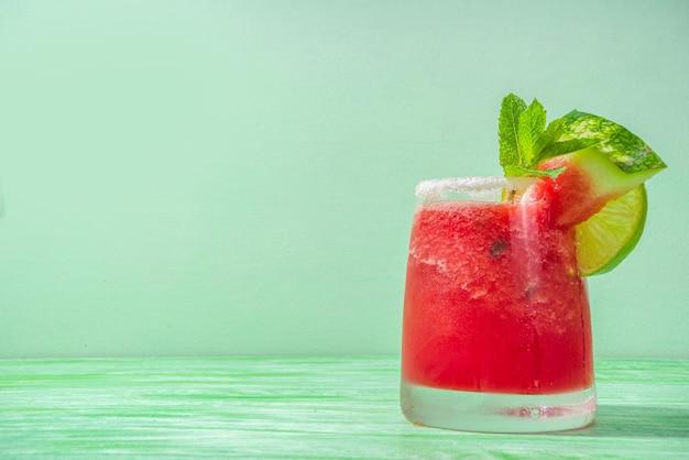 Cocktail estivo freddo, margarita all'anguria o mojito con fette di anguria e lime, ghiaccio tritato e menta. bevanda rinfrescante stagionale, su sfondo illuminato dal sole verde brillante