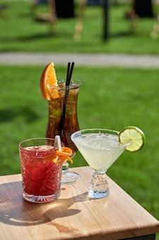 Deliziosi cocktail estivi freddi con lime, menta e ghiaccio in un bicchiere con gocce. cocktail multicolore di alcol al bar.